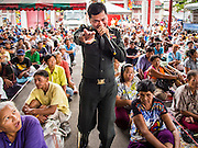 "09 AUGUST 2014 - BANGKOK, THAILAND:   A policeman sings karaoke to keep people entertained at the Ruby Goddess Shrine in the Dusit section of Bangkok. The seventh month of the Chinese Lunar calendar is called ""Ghost Month"" during which ghosts and spirits, including those of the deceased ancestors, come out from the lower realm. It is common for Chinese people to make merit during the month by burning ""hell money"" and presenting food to the ghosts. At Chinese temples in Thailand, it is also customary to give food to the poorer people in the community.        PHOTO BY JACK KURTZ"