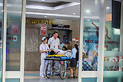 "30 NOVEMBER 2012 - BANGKOK, THAILAND: Volunteer medics with the Ruamkatanyu Foundation check a woman who collapsed on a Bangkok street into Police General Hospital during a Friday night shift. The Ruamkatanyu Foundation was started more than 60 years ago as a charitable organisation that collected the dead and transported them to the nearest facility. Crews sometimes found that the person they had been called to collect wasn't dead, and they were called upon to provide emergency medical care. That's how the foundation medical and rescue service was started. The foundation has 7,000 volunteers nationwide and along with the larger Poh Teck Tung Foundation, is one of the two largest rescue services in the country. The volunteer crews were once dubbed Bangkok's ""Body Snatchers"" but they do much more than that now.    PHOTO BY JACK KURTZ"