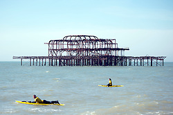 © Licensed to London News Pictures. 29/03/2014. Brighton, UK. People on surf boards in the water.  People enjoy the sunny weather in Brighton today 29th March 2014. The warm weather is forecast to remain into next week. Photo credit : Stephen Simpson/LNP