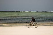 A man riding a bicycle along the beach at Paje, Zanzibar, Tanzania