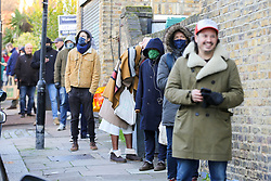 © Licensed to London News Pictures. 24/12/2020. London, UK. People wearing face coverings queue outside Baldwins Butchers in north London to collect their meat products for Christmas. Photo credit: Dinendra Haria/LNP
