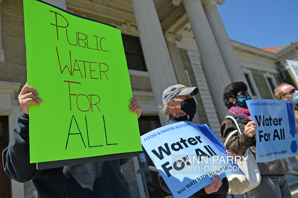 Mineola, New York, USA. April 26, 2021. Activists hold sign saying PUBLIC WATER FOR ALL, and Food and Water Watch signs: WATER FOR ALL!  Faced with a 26% rate increase from New York American Water going into effect May 1, 2021, activists and residents who are NYAW customers rally to urge NYS Assemby to push through legislation, before that date, corresponding with NYS Senate Bill S989A to establish a Nassau County Water Authority and except water works corporations in counties of populations over one million from a special franchise tax.