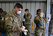 Members of the Illinois National Guard suit up in personal protective gear Thursday, March 26, 2020 to begin shifts at their coronavirus testing facility on the Northwest Side. (Brian Cassella/Chicago Tribune)