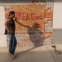 """Ray Nichols takes a break from hanging a plywood sheet that reads """"IRENE 2011"""" over the windows of Beach Bumz bar in Carolina Beach, N.C., Wednesday, October 5, 2016. Southeaster North Carolina is preparing for the possible effects of Hurricane Matthew. Photo by Michael Cline Photography"""