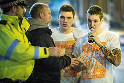 """© Licensed to London News Pictures . 15/11/2015 . Manchester , UK . A police officer alcohol from people drinking in the street . Annual student pub crawl """" Carnage """" at Manchester's Deansgate Locks nightclubs venue . The event sees students visit several clubs over the course of an evening . This year's theme is """" Animal Instinct - unleash your beast """" . Photo credit : Joel Goodman/LNP"""