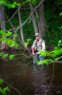 Fly fisherman deep in the woods.