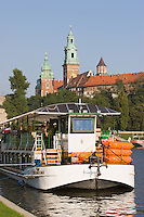 Tourist boat and the Wawel Cathedral on the Vistula River in Krakow Poland