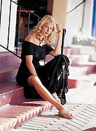 Photograph of a blonde model resting on the steps in her black gauze dress - created for Boston Proper website and catalog.