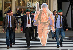 © Licensed to London News Pictures.28/03/2017.London, UK. Former Royal Marines carry a cardboard cutout image of Sgt Blackman as they arrive at the Royal Courts of Justice in London, where a judge reduced the sentence for Sgt Blackman's manslaughter charge, meaning he will be free within weeks..Photo credit: Ben Cawthra/LNP