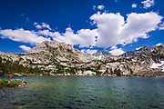 Hiker on the shore of Treasure Lake under the Sierra Crest, John Muir Wilderness, Sierra Nevada Mountains, California USA