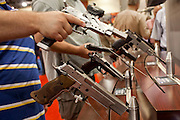 16 MAY 2009 -- PHOENIX, AZ: People look at Sig Sauer handguns in the Sig booth at the NRA convention in Phoenix Saturday. About 60,000 people were expected to attend the trade show at the 138th annual National Rifle Association Annual Meeting in the Phoenix Convention Center in Phoenix, AZ. Photo by Jack Kurtz
