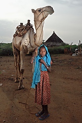 """Kadija's daughter Saidya, 11,  stands with a neighbor's camel she takes cares of outside her home in  Barentu, Eritrea august 25, 2006. Kadija is a traditional birth assistant as well as a recipient of a donkey from the women's union """"Hamade"""". (Ami Vitale)"""