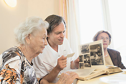 Caretaker watching photos with senior women at rest home, Bavaria, Germany