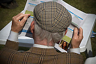 An elderly man wearing traditional Tweed jacket and cap reading the official programme on the opening weekend of the the Edinburgh International Book Festival. The three-week event is the world's biggest literary festival and is held during the annual Edinburgh Festival. The 2012 event featured talks and presentations by more than 500 authors from around the world.