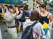 03 SEPTEMBER 2015 - BANGKOK, THAILAND: A security guard at Erawan Shrine tells tourists he will have to check their bags at the gate to the shrine Thursday. Security at the shrine has been stepped up since the bombing. Repairs to Erawan Shrine were completed Thursday, Sept 3 after the shrine was bombed on August 17. Twenty people were killed in the bombing and more than 100 injured. The statue of the Four Faced Brahma in the shrine was damaged by shrapnel and a building at the shrine was damaged by debris.    PHOTO BY JACK KURTZ
