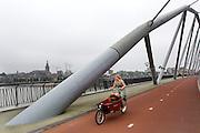 Een vrouw fietst bij Nijmegen met een bakfiets over de Snelbinder dat onderdeel is van het Rijn-Waalpad, de snelfietsroute tussen Arnhem en Nijmegen. Als de route helemaal klaar is, kunnen fietsers binnen 40 minuten van Arnhem naar Nijmegen fietsen. De snelfietsroute kent weinig obstakels en moet het aantrekkelijk maken om ook langere afstanden met de fiets af te leggen.<br /> <br /> A woman rides with a cargo bike near Nijmegen at the Snelbinder bridge that is part of the Rijn-Waalpad, the fast cycling route between Arnhem and Nijmegen. When the route is finished, cyclists can get within 40 minutes from Arnhem to Nijmegen. The fast cycle route has few obstacles and to make it attractive to commute long distances by bicycle.