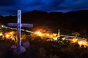 A wooden cross looms over the church and town of Jemez Springs, New Mexico at night on August 5, 2006.