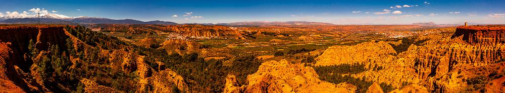 Panoramic view of Badlands from Mirador del Fin del Mundo (the towns of Purullena-far left, Los Banos-above, center and Purullena-far right), near Guadix, Granada Province, Andalusia, Spain.