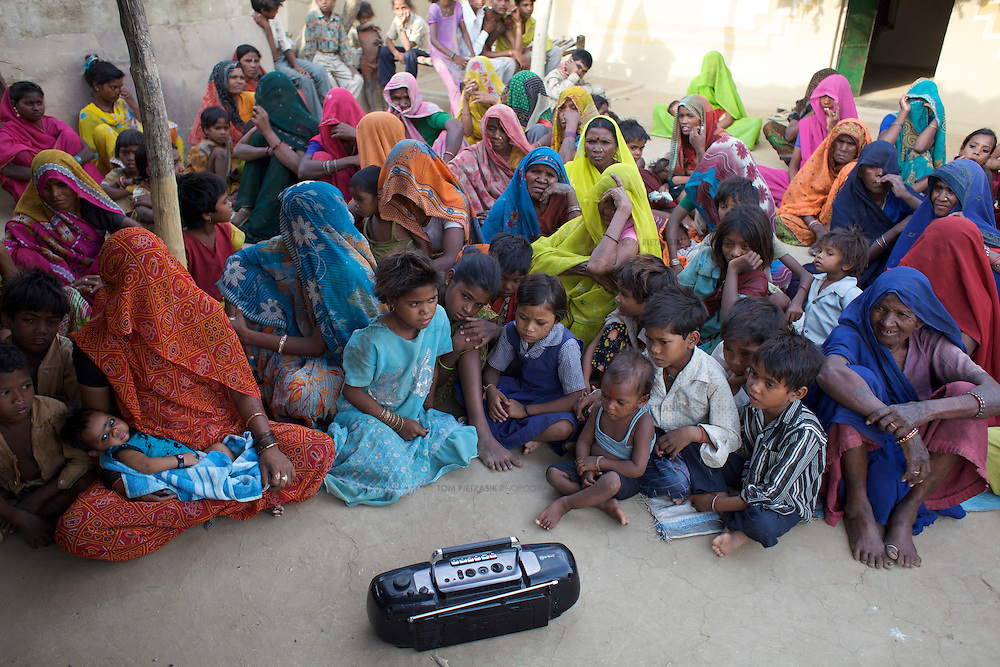 """A drama, made by Dharkan 107.8 on the theme of institutional delivery is played to an audience of women and children in the Adivasi (tribal, or Scheduled Tribe) village of Patara, 20km from Shivpuri. Before the official launch of the community radio station in July 2009, Vandana and her colleagues have recorded several programs informing women of government health services. They call the airing of these pilot shows """"narrowcast"""" in anticipation of the imminent """"broadcast"""". These narrowcasts help staff at Dharkan 107.8 appraise their programming. ..Shivpuri district in Madhya Pradesh suffers from poor health outcomes. Of particular concern is the high rate of maternal mortality. One of the Indian government's aims, with partners Unicef, is to encourage the population to adopt practices to improve sanitation and health practices. In an area made up of traditionally disadvantage groups and suffering low literacy rates, this can be a challenge. ..A survey found that radio was the most readily accessible media by the Shivpuri community with more than half saying they tuned in several times a day. ..Dharkan 107.8 FM will go on air in July. The station that will broadcast to 75 villages in a 15-kilometer radius reaching 170,000 people...Rather than preaching educational messages, the station, which is already producing pilot programs, uses humor and folk artists performing in the local language to entertain and inform their audiences. There is a major impact, especially on women, who are contributing their voices to such wide-ranging issues as caste discrimination, female feticide and women's empowerment. ..Photo: Tom Pietrasik.Shivpuri, Madhya Pradeh. India.June 2009"""