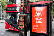 As the UKs Conornavirus pandemic lockdown continues, but with travel restrictions and social distancing rules starting to ease after three months of closures and isolation, a London bus drives past a bus stop where advertising advises the public to wear face coverings on all public transport from June 15th next week, on 9th June 2020, in London, England.