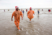 Two men dressed as Christmas turkeys. Participants dressed up for Folkestone Lions Club Boxing Day Dip.  An annual fancy dress fundraising event, where all sorts of amusing costumes and characters enter the cold sea of the English Channel at Sunny Sands, Folkestone. UK.