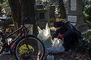 A nun takes care of a grave with flowers and candles in Rakowicki cemetery in Krakow, Poland in 2019.