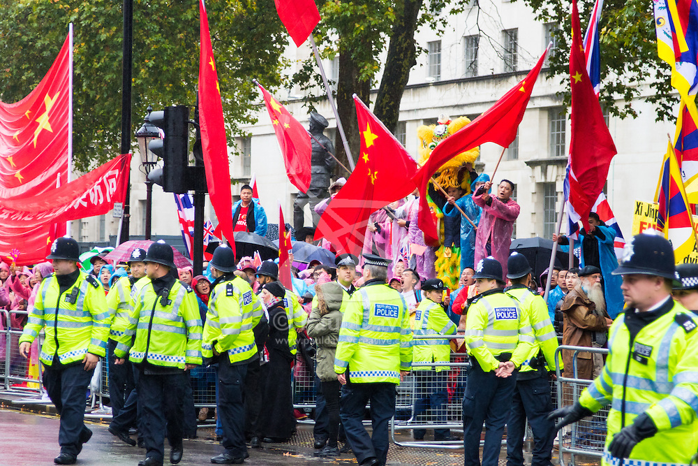"Whitehall, London, October 21st 2015. Hundreds of Chinese supporters waving banners and wearing ""I Love China"" T-shirts apparently supplied by the Chinese embassy, face Human rights, Tibetan and Falun Gong protesters as they await the arrival at Downing Street of President Xi Jinpeng."