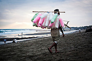 A cotton candy vendor walks along Echo Beach looking for customers, Bali, Indonesia, Southeast Asia