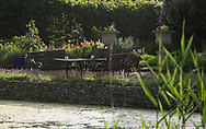 A view over the moat to a seating area surrounded by Lupinus in the formal garden at Hindringham Hall, Hindringham, Norfolk