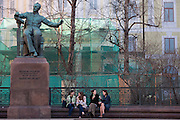 Moscow, Russia, 26/04/2011..Music students sit under a  statue of Russian composer Pyotr Tchaikovsky in front of the Moscow Conservatory, which is currently undergoing extensive renovation.