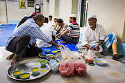 26 JULY 2013 - BANGKOK, THAILAND:   Men relax in the dining area at Haroon Mosque while they wait to start Iftar. Iftar is the Muslim meal that breaks the day long fast during Ramadan. Ramadan is the ninth month of the Islamic calendar, and the month in which Muslims believe the Quran was revealed. The month is spent by Muslims fasting during the daylight hours from dawn to sunset. Fasting during the month of Ramadan is one of the Five Pillars of Islam. Muslims believe that the Quran was sent down during this month, thus being prepared for gradual revelation by Jibraeel (Gabriel) to the prophet Muhammad.        <br />       PHOTO BY JACK KURTZ
