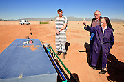 "18 MARCH 2010 - SURPRISE, AZ: County inmate Robert Henderson watches Sister Mary Ruth Dittman (CQ) sprinkle holy water on a casket in White Tanks Cemetery on Camelback Rd. in an unincorporated part of the county near Surprise. The county spent about $2.5 million to inter indigent people in what is Maricopa County's ""potters field."" About 3,000 people, children and adults, are buried in the dusty field west of Phoenix.        PHOTO BY JACK KURTZ"