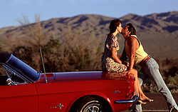 couple kissing on top of a vintage car in the desert of California