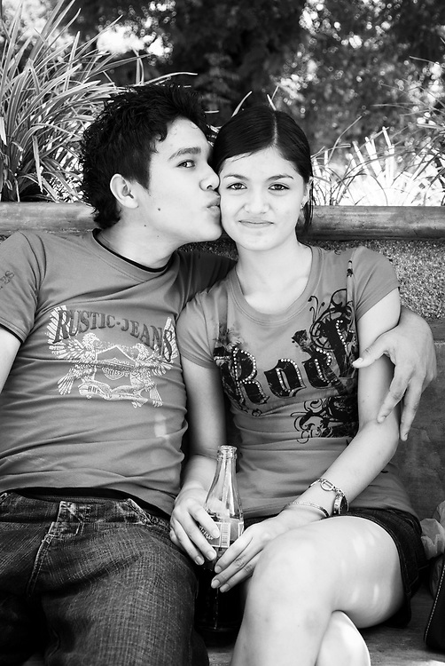 David, Panama - December 17, 2008: A girl gets a kiss from her boyfriend at a park in David.