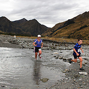 Runners Oliver Bixley and Ann Bixley crosses  Moke Creek on the Ben Lomond High Country Station during the Pure South Shotover Moonlight Mountain Marathon and trail runs. Moke Lake, Queenstown, New Zealand. 4th February 2012. Photo Tim Clayton