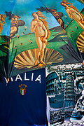 Images of the famous painting of Venus printed on umbrella alongside T-shirts on sale in a tourist stall in Florence, Italy.