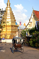 A rickshaw passes by Wat Chomphu complex.  Once upon a time Chiang Mai had hundreds of these rickshaws plying the streets for fares.  Considering modern day Chiang Mai's traffic, the old rickshaws are relegated to mere short trips on the city's back streets and alleyways.