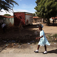 A young school girl walks along the side of the road in northern Haiti.