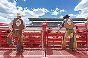 Rodeo riders get ready during bronco riding competition during the Cheyenne Frontier Days rodeo July 25, 2015 in Cheyenne, Wyoming. Frontier Days celebrates the cowboy traditions of the west with a rodeo, parade and fair.