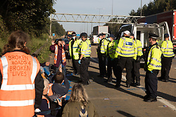 Ockham, UK. 21st September, 2021. Surrey Police officers arrest Insulate Britain climate activists who had previously blocked the clockwise carriageway of the M25 between Junctions 9 and 10 as part of a campaign intended to push the UK government to make significant legislative change to start lowering emissions. Activists briefly halted traffic on both carriageways of the motorway before being removed and arrested by Surrey Police.