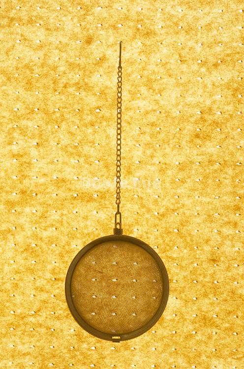 tea strainer against perforated paper