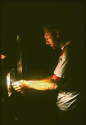 Trucker Fixing Headlamp On Haul Road