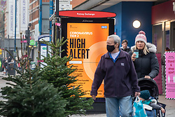 © Licensed to London News Pictures. 08/12/2020. London, UK. Shoppers walk past a Tier 2 Covid-19 High Alert sign in Putney, South West London as the government warn the general public not to let their guard down over covid safety during the vaccine rollout. Today a 90 year old grandmother, Margaret Keenan became the first person in the World to get an approved Pfizer Covid-19 vaccine as the government and NHS has kicked off the biggest vaccination drive in UK history. Photo credit: Alex Lentati/LNP