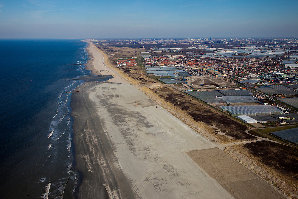Nederland, Zuid-Holland, 's-Gravenzande, 18-03-2009; Versterking van de kust van Delfland tussen Ter Heijde en 's-Gravenzande door middel van zandsuppletie. Het strand onder in beeld is breder, hier is al gesuppleerd, verder naar horizon moet er nog zand opgespoten worden. Het strand is extra breed gemaakt om een tweede duinenrij met duinvallei te maken,  natuurcompensatie in verband met de aanleg van de Tweede Maasvlakte. Op het verbreedde strand is helm aangeplant om wegstuiven van het zand te voorkomen, rechtsonder. De Delflandse kust is een van de 'zwakke schakels'..The coast of Delfland, between Hoek van Holland and The Hague, is being strengthened by means of sand-supplementation. The beach in the lower part of the picture is wider, sand has already been supplemented, in the direction of the horizon sand still needs to be sprayed onto the beach. .Extra sand has been applied to make an extra dune valley on the beach. This so-called nature compensation is necessary because of the construction of the nearby Maasvlakte 2 (land reclamation for Port of Rotterdam). Marram grass has been planted to keep the new sand in its place (bottom right)..Swart collectie, luchtfoto (toeslag); Swart Collection, aerial photo (additional fee required); .foto Siebe Swart / photo Siebe Swart