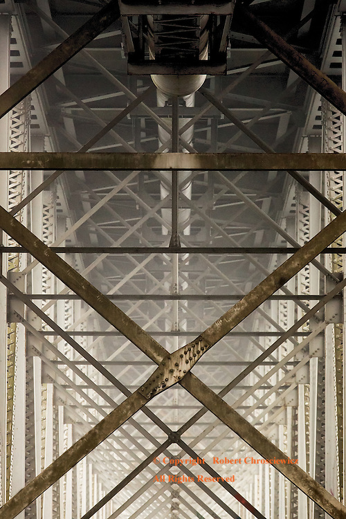 Vanishing Iron Works: Morning fog slowly lifts revealing the repetition of geometric patterns, found in the metal work of a dated bridge and takes on a surrealistic sense as one gazes down its vanishing point, Rosedale-Agassiz British Columbia Canada.