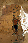 Hiker climbs the rope ladder in a water eroded cave at Barak Stream, Aravah Desert,  Israel,