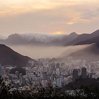 Clouds spill over the hills surrounding Rio de Janeiro at sunset.