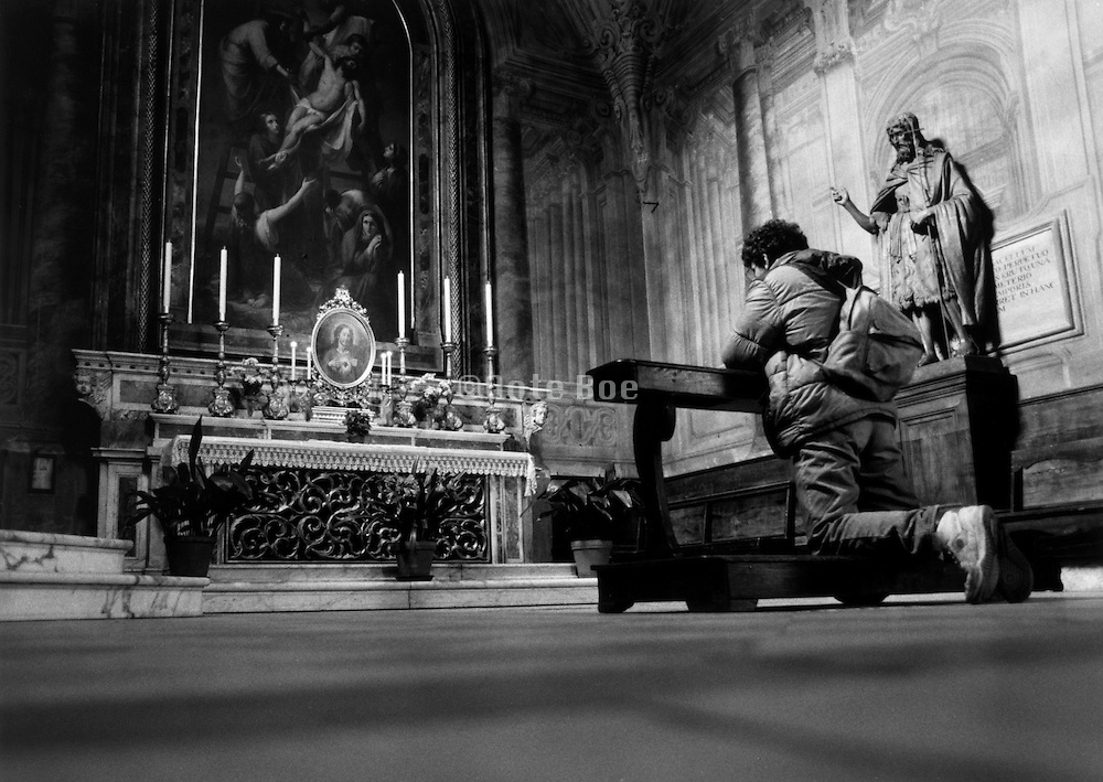Young man on his knees praying in church Italy.