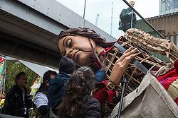 London, UK. 23rd October, 2021. Little Amal, a giant puppet of a Syrian refugee girl fleeing conflict, is carefully manoeuvred beneath the Millennium Bridge en route from St Paul's Cathedral to the Globe Theatre. The 3.5-metre puppet, which is nearing the end of an 8,000km journey from the Turkish-Syrian border to Manchester in support of refugees, earlier climbed the steps of St Paul's Cathedral to present a wood carving of a ship at sea from St Paul's birthplace at Tarsus in Turkey to the dean.