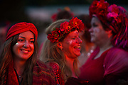 Glastonbury Festival, 2015.<br /> Women from a festival choir, dressed in red, smiling together and laughing, launching the start of the Glastonbury Festival